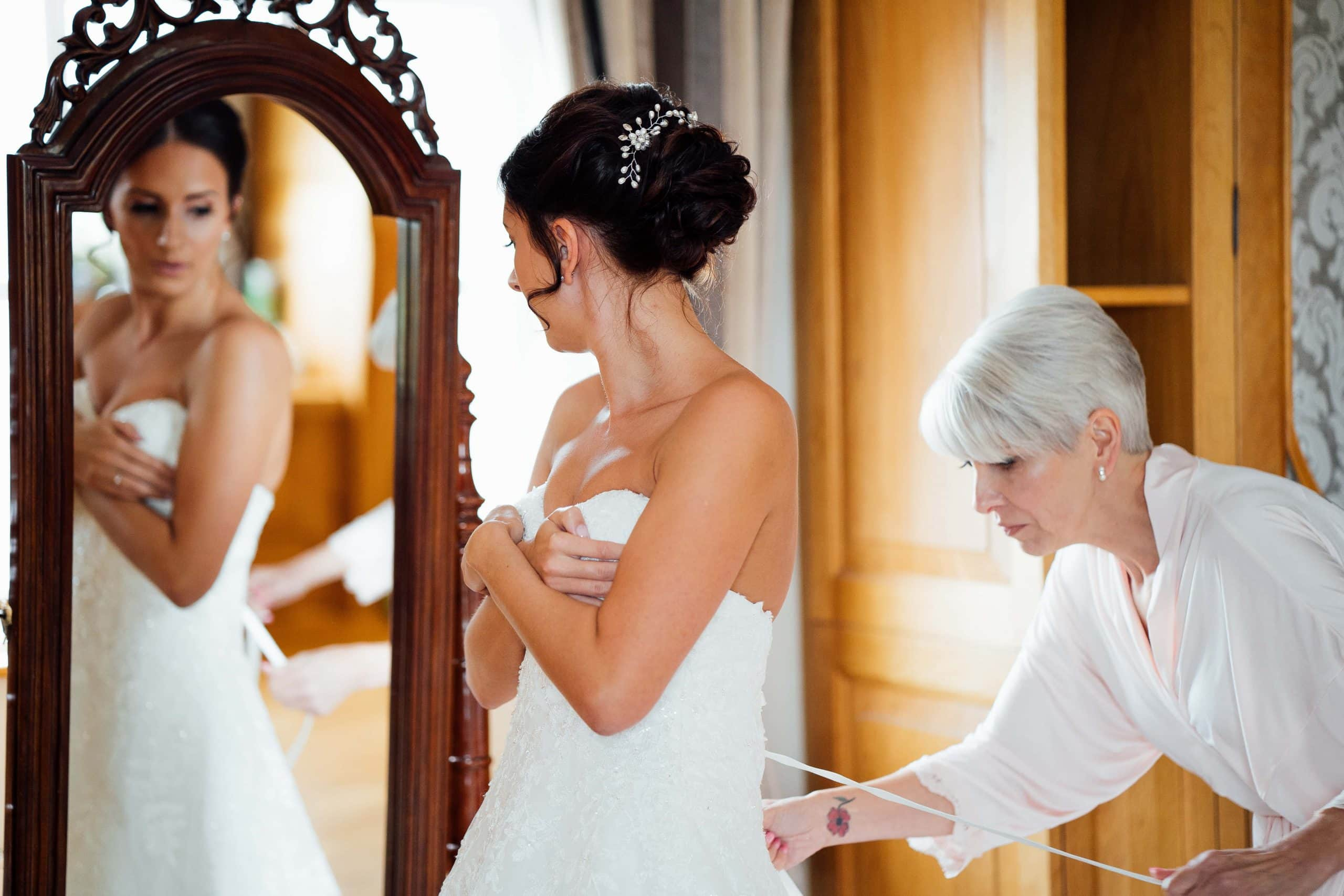 Bride being helped in to dress by mother