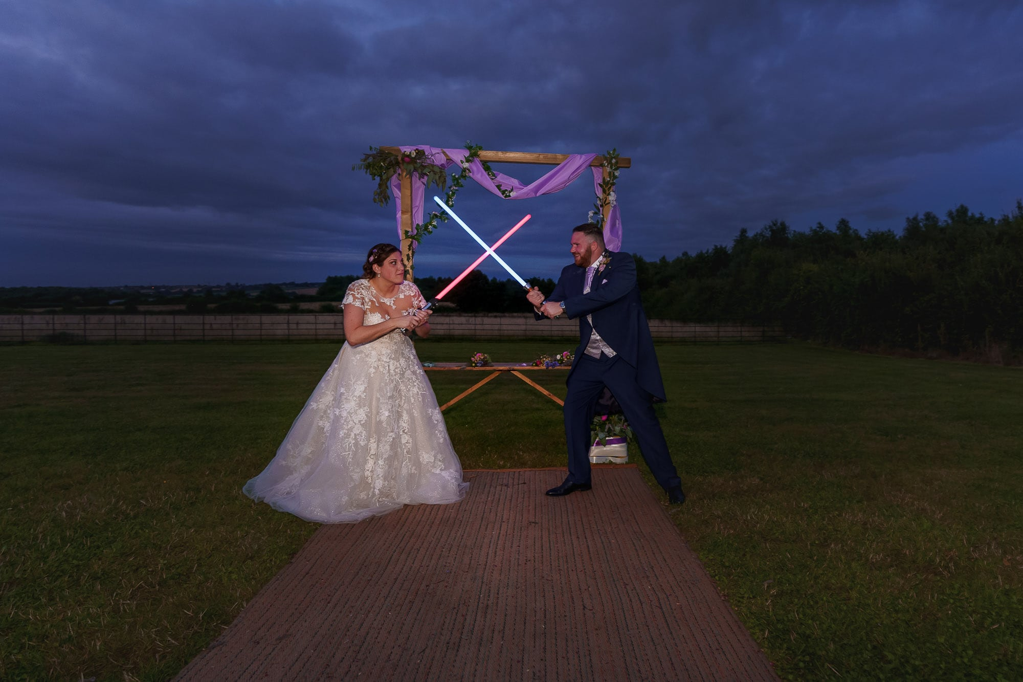 bride and groom with light sabers on wedding day