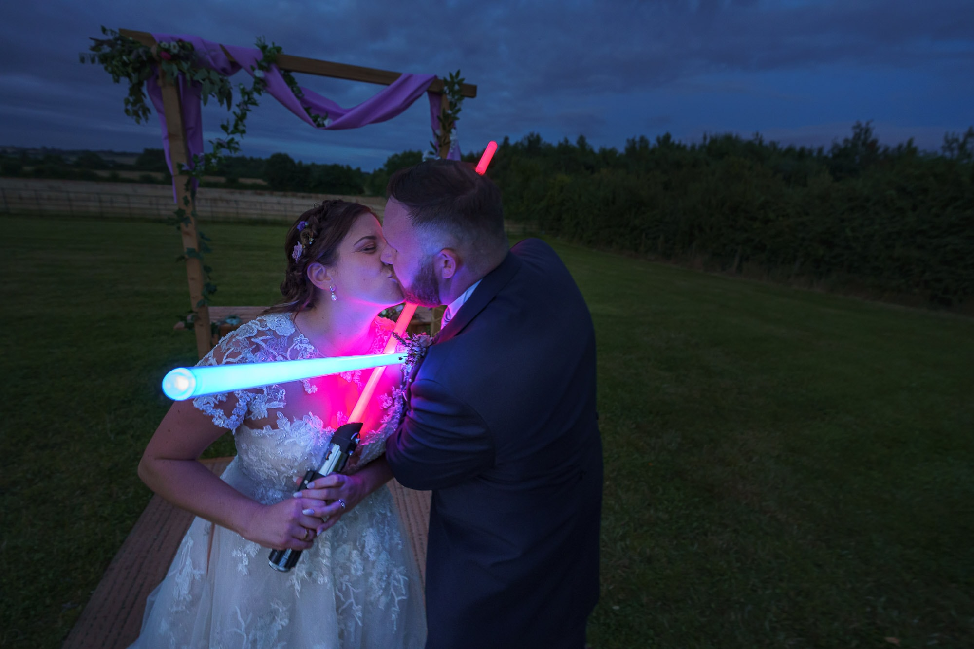 bride and groom with light sabers at stretton manor barn wedding