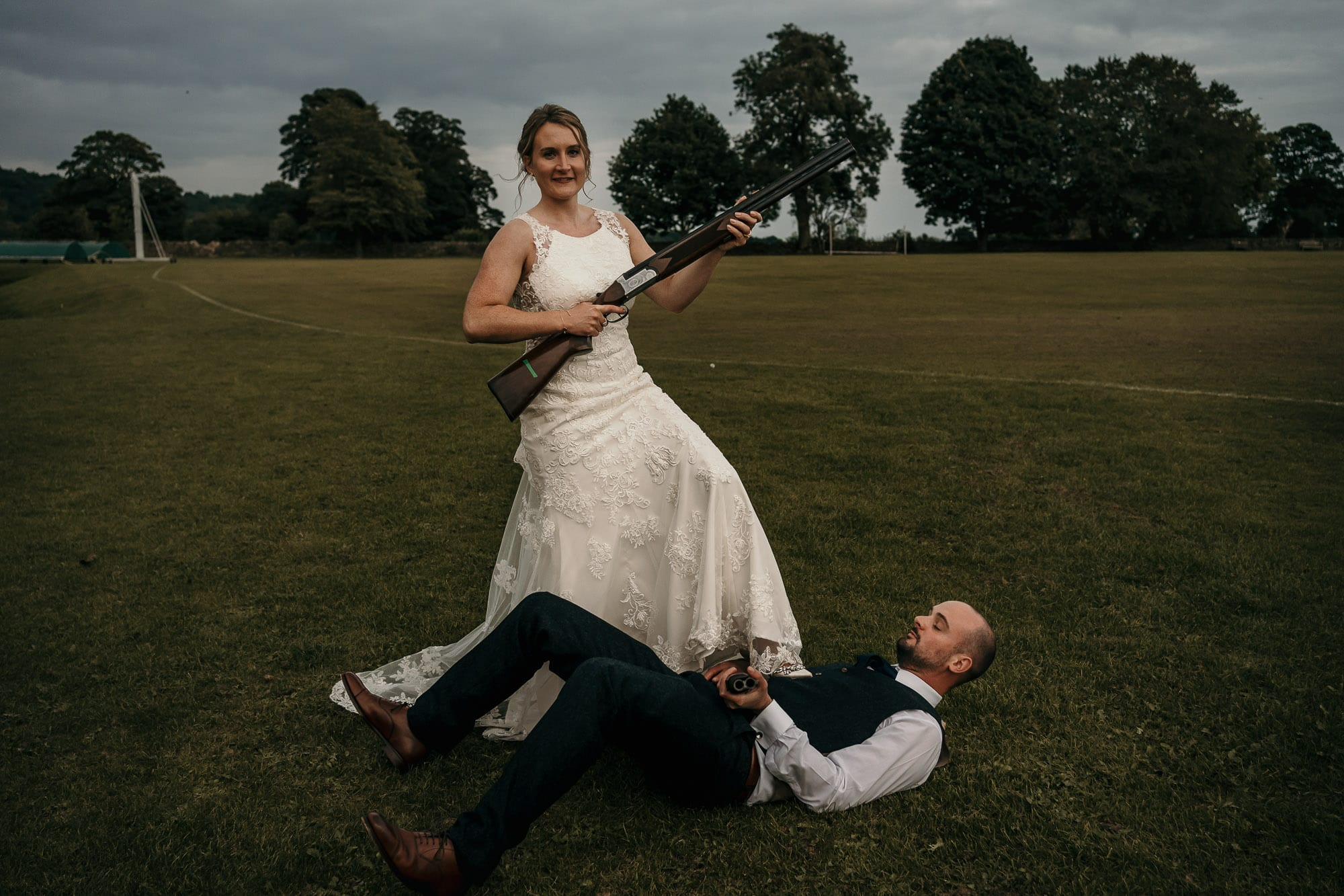 Bride and groom with gun on wedding day